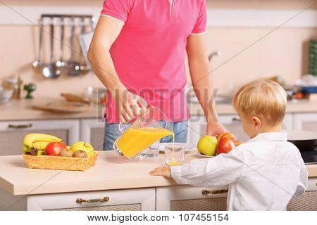 Dad pours orange juice for his son.