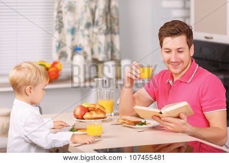 Father and his son are having fine breakfast.
