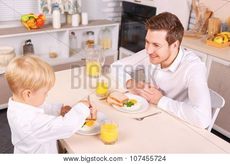 Attentive dad watches his son eating.