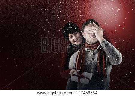 Woman giving man a present against snow