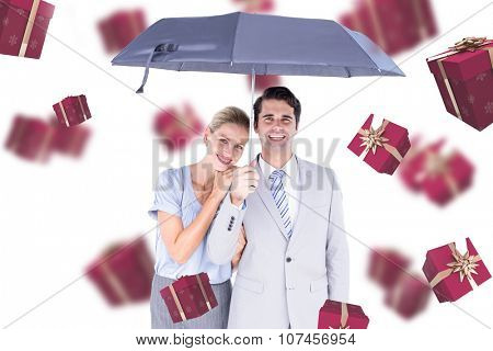 Business people holding a black umbrella against red presents