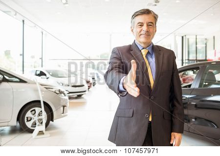 Businessman ready to shake hand at new car showroom