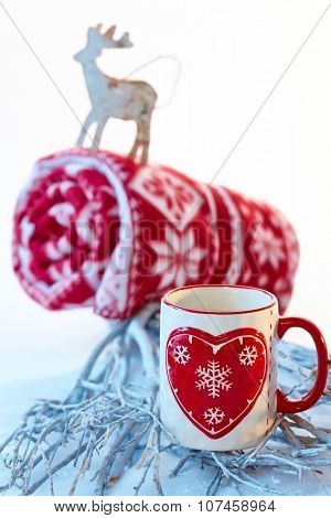 Christmas still-life in red and white with mug and reindeer.