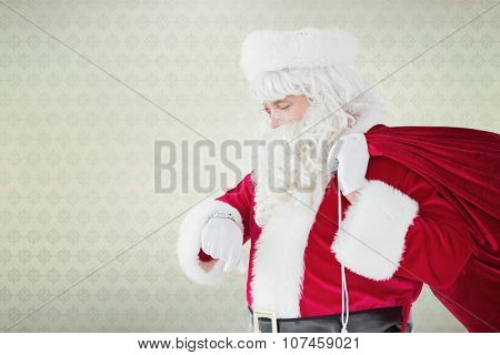 Festive santa claus checking time against room with wooden floor