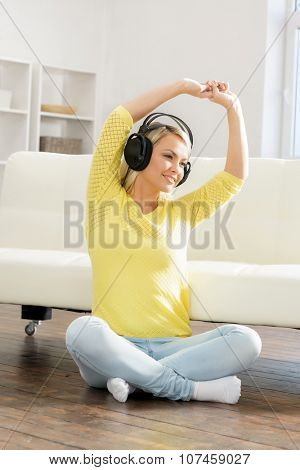 Young and beautiful teenage girl listening to the music at home