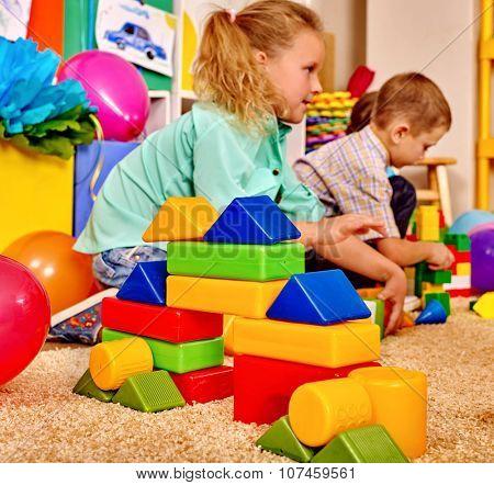 Group children playing blocks on floor in kindergarten . Top view.