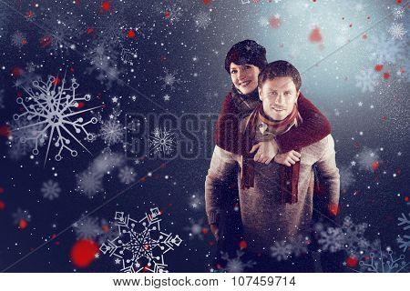 Man giving girlfriend piggy back against snow