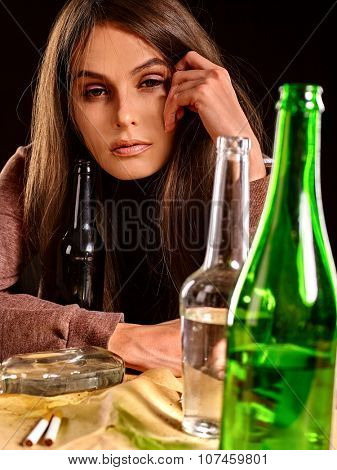 Drunk girl sitting near bottle of alcohol. Soccial issue alcoholism.