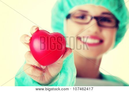 Smiling female doctor or nurse in surgical clothes holding red heart