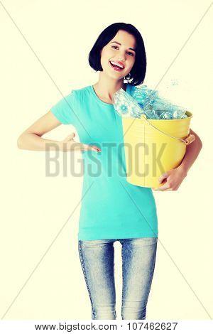 Beautiful young woman holding recycling bin.