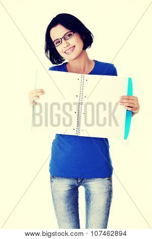 Studying happy young woman showing blank pages of her notebook for school.