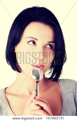 Portrait of young smiling woman with spoon in her mouth -pleasure from eating