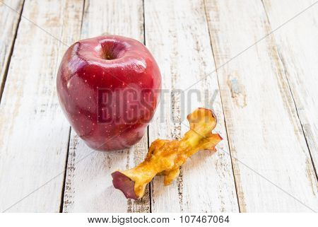Red Apple And Apple Core On A White Wooden Background