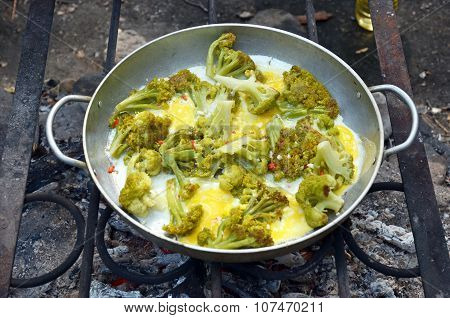 Fried Eggs With Broccoli, Cooked In A Large Frying Pan Over A Campfire