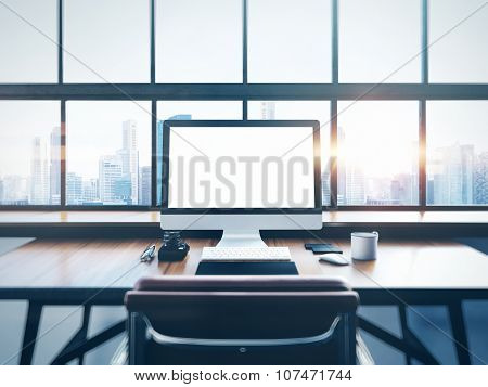 Photo of modern workspace with panoramic windows.  City at sunrise in the background. 3D rendering