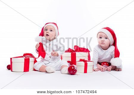 Two Beautiful Baby In The New Year's Cap And White Body Sitting Among Festive Boxes With Gifts And C
