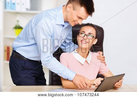 Male employee cuddles his office girlfriend.