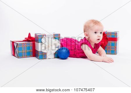 Cute Girl Lying On Her Stomach On A White Background In A New Year's Cap Among Christmas Balls, Blue
