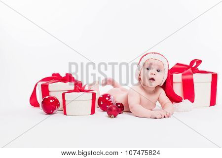 Cute Baby Girl Lying Naked On Her Stomach On A White Background In A Red New Year's Cap Among Red Ch