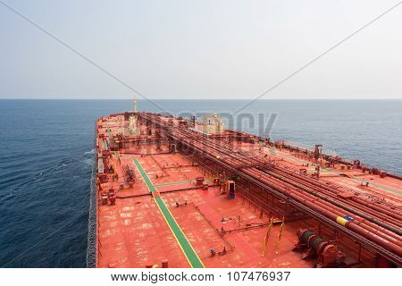 Oil carriers deck with pipeline under clear sky.