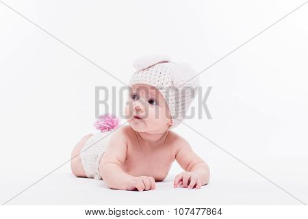 Cute Baby Girl Lying Naked On A White Background Wearing A Hat In The Form Of A Christmas Bunny