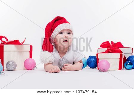 Cute Baby Lying On His Stomach In A New Year's Cap Among Christmas Toys And Blue And Red Boxes With