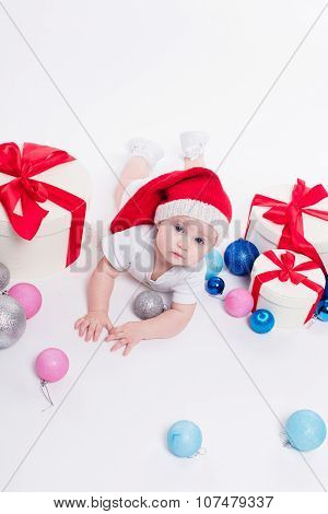 Cute Baby Lying On His Stomach In A New Year's Cap Among Christmas Toys And Blue And Red Boxes