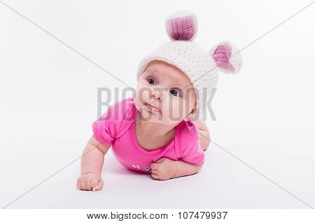 Cute Baby Girl Lying In A Bright Red T-shirt On A White Background Wearing A Hat In The Form