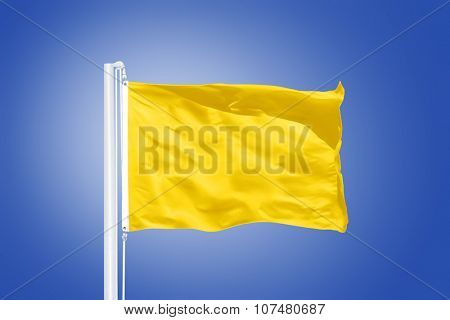 Yellow flag flying in a stiff breeze against clear blue sky.