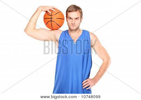 Young Basketball Player Standing And Holding A Basketball