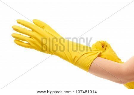 Close up of female hands putting on yellow protective rubber gloves