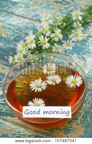 Good morning card with cup of chamomile tea and fresh chamomile flowers