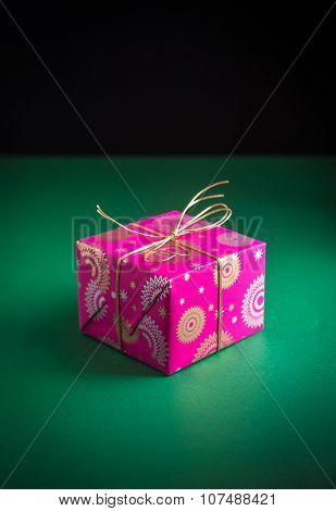 A bright pink color small gift pack tied with golden string. A festive gift and rewards.