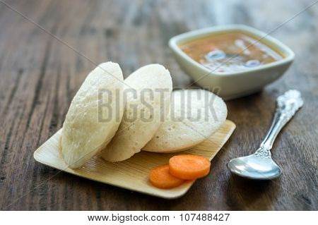 Close up of steamed idlis in an eco-friendly plate and bowl of spicy sambar.