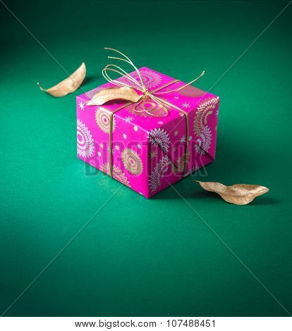 Beautiful small gift box wrapped with bright pink wrapping paper and arranged with dry golden leaves. Festive object and background.