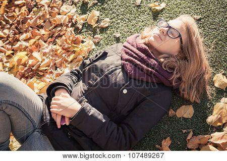 Beautiful Blond Teenage Girl Laying In Autumnal Park