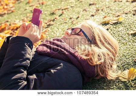 Teenage Girl Laying In Park And Using Cellphone