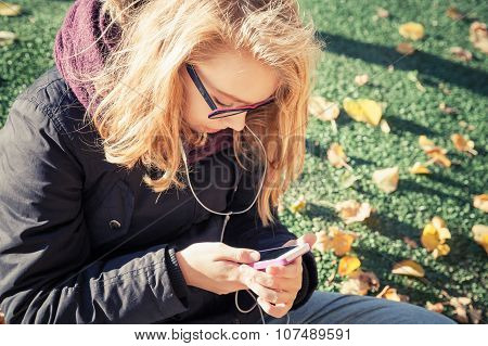 Girl In Glasses Sitting In Park And Using Smartphone