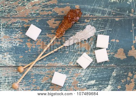 White sugar cubes and white and brown sugar sticks on rustic wooden surface