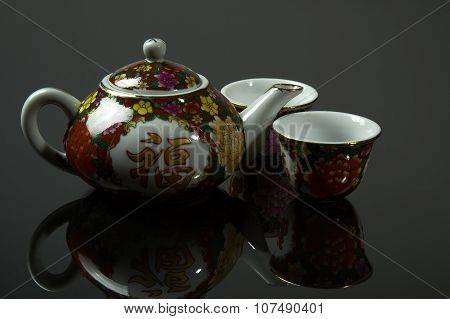Chinese Jug And Two Cups With Mirrored Reflection On Isolateg Gray
