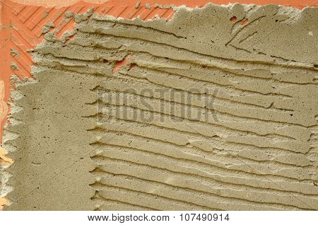 Embossed reverse side of small tile with dry plastering
