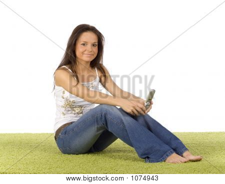 Young Woman With Cell Phone On The Green Carpet