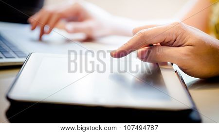 Hand Touching Screen On Modern Digital Tablet Pc. Selective Focus On Finger. With Hand Playing Lapto