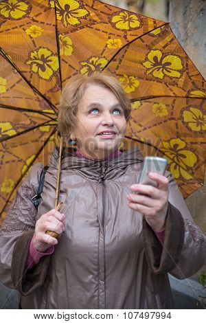 Old pensioner woman with umbrella and phone