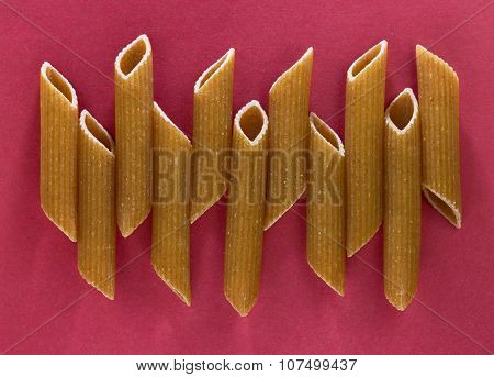 Penne pasta on the red background