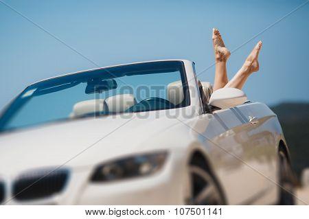 Slender women's legs look out of car window