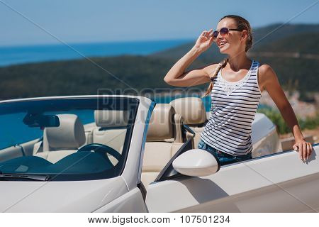 Beautiful woman in a white convertible car
