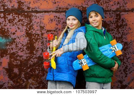 Smiling boy and girl holding color plastic penny boards or skateboards outdoor