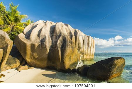 Beautifully shaped granite boulders reflecting in the water at Anse Source d'Argent beach, La Digue island, Seychelles