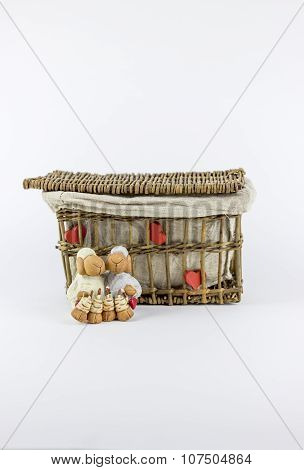 Two Sheep Figurines In Front Of A Vintage Rattan Basket